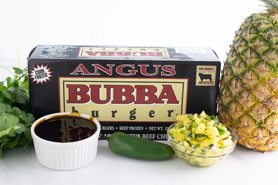 Aungus BUBBA Burger box on a marble counter top surrounded by fresh pineapple and cilantro, homemade bourbon teriyaki, and pineapple salsa