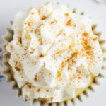 Overhead picture of a cupcake topped with Whipped Mascarpone Frosting and a sprinkle of cinnamon
