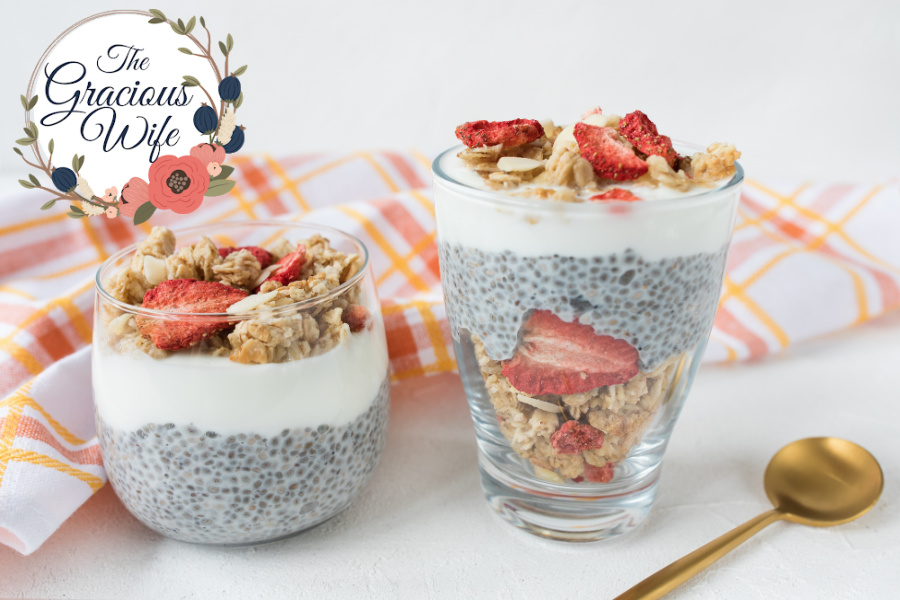 Chia pudding in a jar and a cup topped with granola and dried strawberries