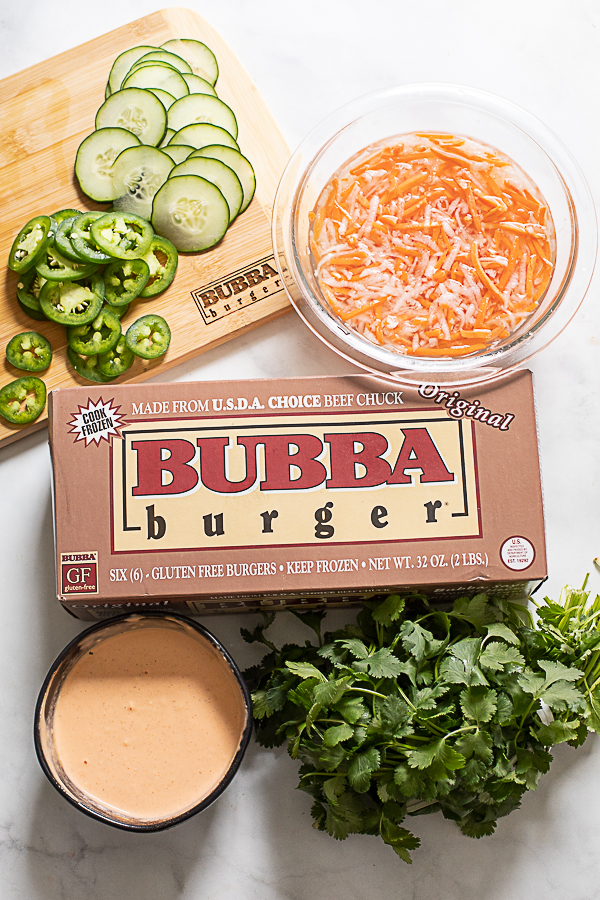 Photo of the ingredients used to make banh mi burgers, including BUBBA burgers, cucumber slices, jalapeno slices, spicy mayo, pickled carrot and daikon, and fresh cilantro.