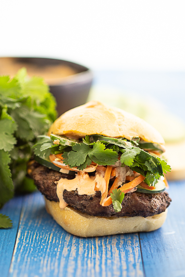 Side view of a fully topped banh mi burger with a little drizzle of spicy mayo running down the side.