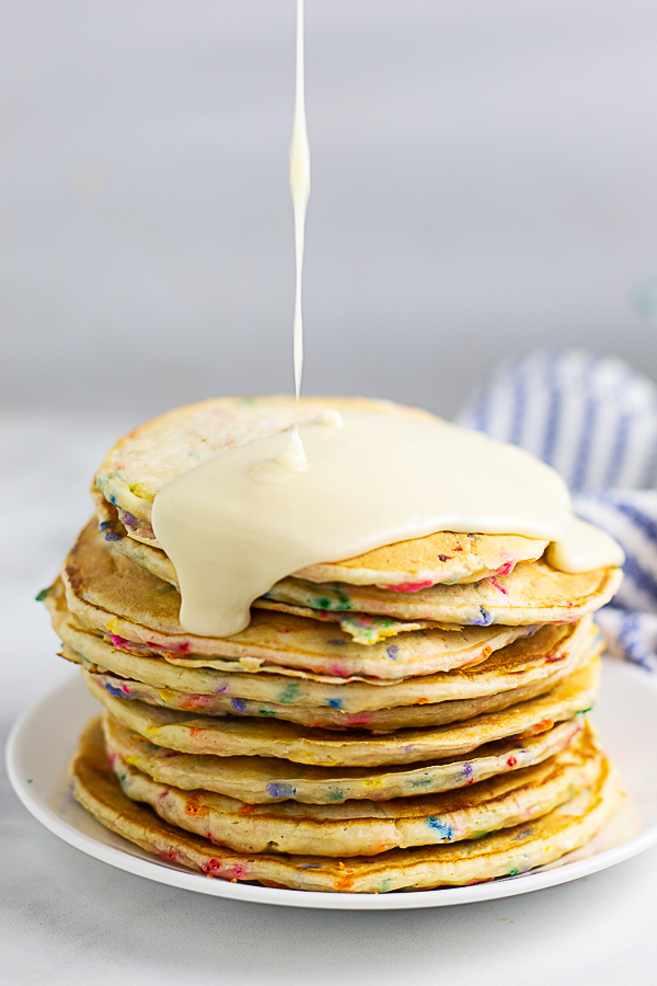 A stack of funfetti pancakes on a small plate being drizzled with vanilla glaze