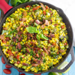 Overhead view of southern succotash in a cast iron skillet topped with bacon and fresh basil surrounded by a clean linen, lime wedges, more fresh basil, and cherry tomatoes