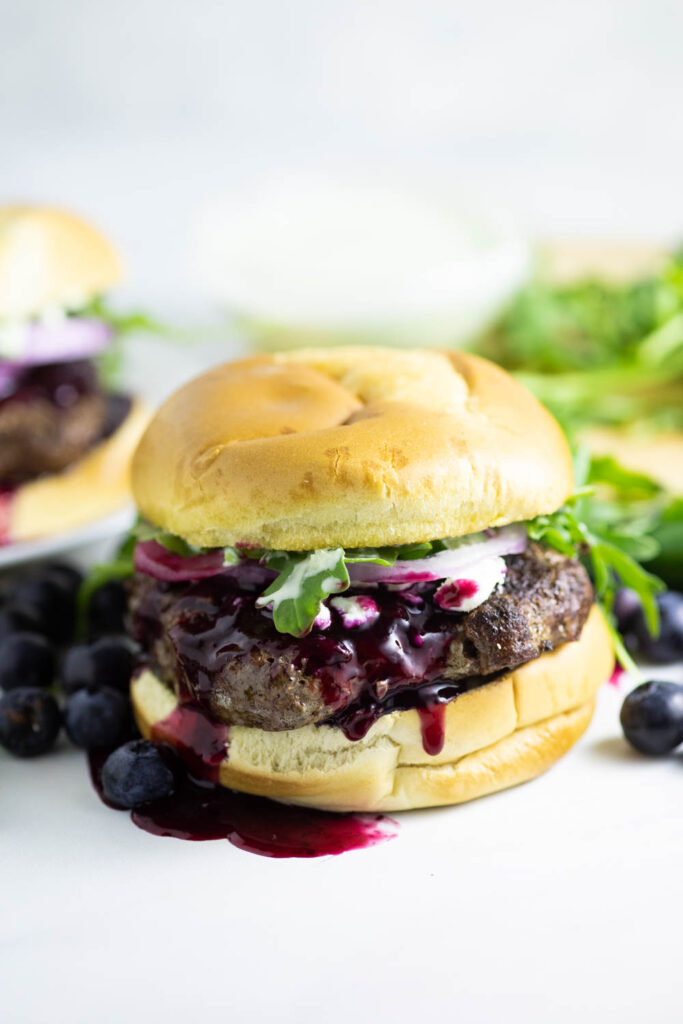 Front view of a spicy blueberry burger with blueberry sauce running down with fresh arugula in the backgrounf