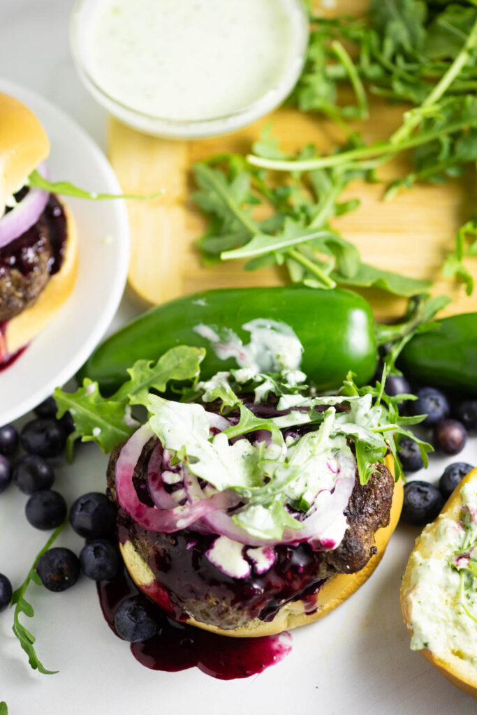 Open face spicy blueberry burger with blueberry sauce dripping down topped with jalapeno aioli, red onion, feta, and arugula surrounded by arugula on a wooden cutting board and fresh jalapenos and blueberries.