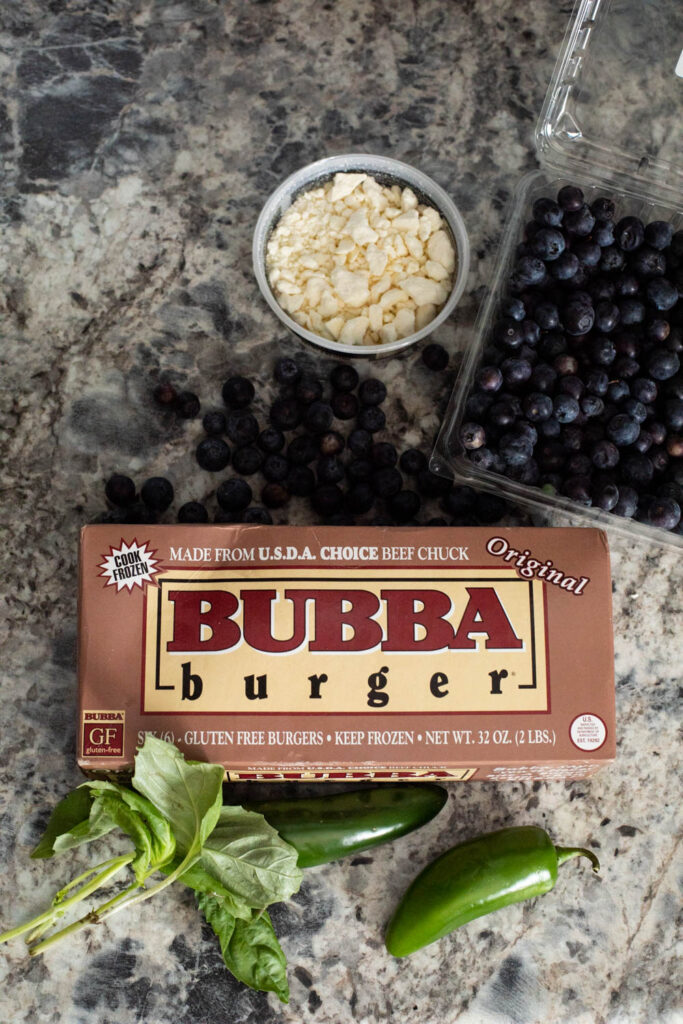 Ingredients to make a spicy blueberry burger, including fresh blueberries, feta cheese, basil, jalapenos, and burgers
